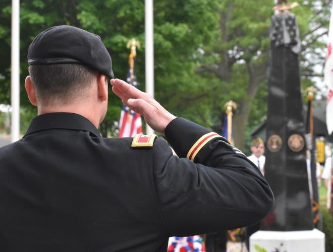 Col. Todd Burnley of Rock Island Arsenal salutes during echo Taps near the end of the Memorial Day observance on Monday, May 31, at the Orion Community Veterans Monument in Central Park