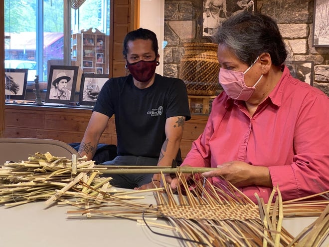 Dylan Morgan watches master basket maker Lucille Lossiah weave a rivercane basket.
