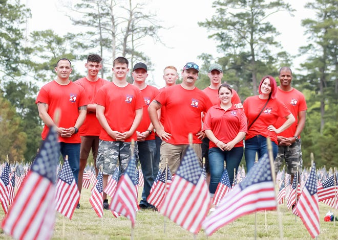 Volunteers with Remember Everyone Deployed (R.E.D.) pose for a photo during a Memorial Day event held at the Coastal Carolina State Veterans Cemetery in Jacksonville, Friday, May 28, 2021.