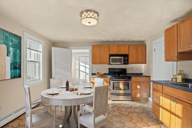 The eat-in kitchen in Unit 1 has paneled maple cabinetry and Frigidaire stainless steel appliances, including four-burner gas cooking and granite-finish laminate counters.