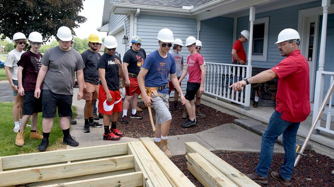 Bedford High School Construction Trades instructor Keven Vogel giving out instructions to the students outside Michael Sulewski home in Temperance to build the handicap ramp.
