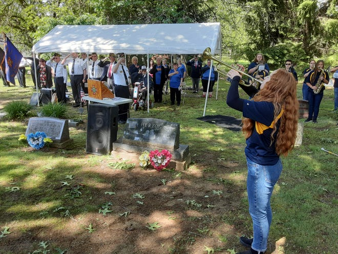 Raina Ciecko, a senior at Airport High School, plays Taps with Echo while veterans and auxiliary members salute during the annual Memorial Day service at Carleton Cemetery Monday morning. Not visible is senior Ryan Lewis, who played echo from another part of the cemetery.