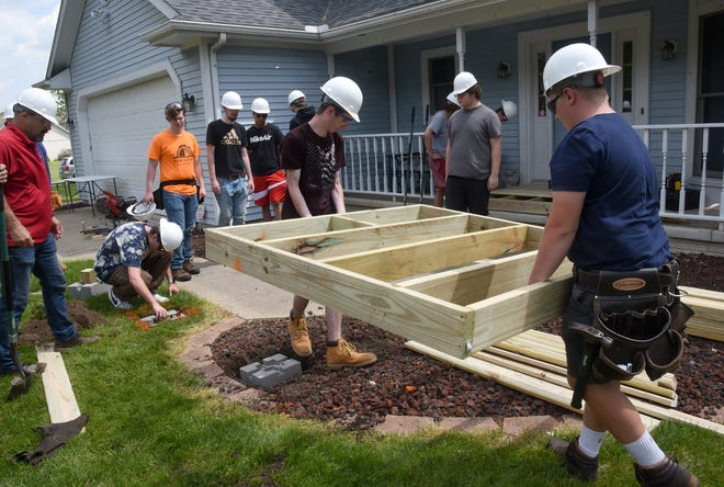 Bedford High School senior Gavin Hamilton and junior Ethan Rogers carry the second base for the handicap ramp as eighteen students from the Construction Trades class build a handicap ramp for Michael Sulewski at his home in Temperance.