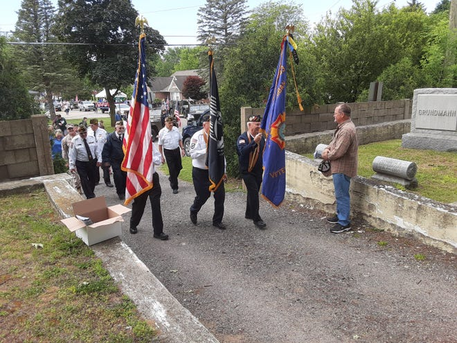 Volunteer Len Presley (far right) hands out programs while color guards for Carleton Post 4093, Veterans of Foreign Wars, and Carleton Post 66, American Legion, pass by at the entrance to Carleton Cemetery where a Memorial Day service was held Monday. The color guards also led a parade through the Village of Carleton as veterans and residents celebrated the holiday.