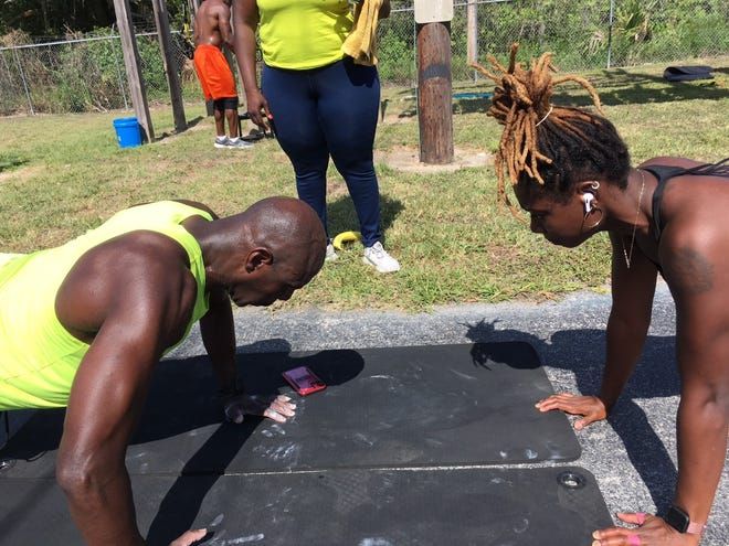 """Neil Alexander, left, gets encouragement in doing push-ups from Jasmine Jackson, right, during the """"Murph"""" tribute workout on Memorial Day at Zone Health & Fitness in Ocala."""