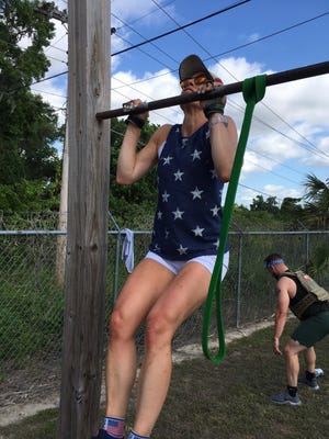"""Dorothy Hughes does pull-ups on Monday during the """"Murph"""" workout at Zone Health & Fitness in Ocala."""