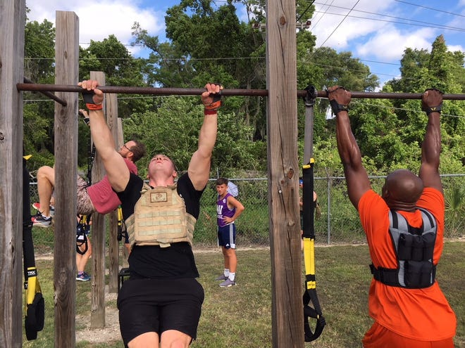 """Marine Lance Cpl. Troy Kaastra, left, and Quentin Boone, right, an RN with Ocala Regional Medical Center, perform pull-ups during the """"Murph"""" Hero Workout on Monday at Zone Health & Fitness. The """"Murph"""" is one of 12 workouts to honor 12 fallen military and first responders heroes."""
