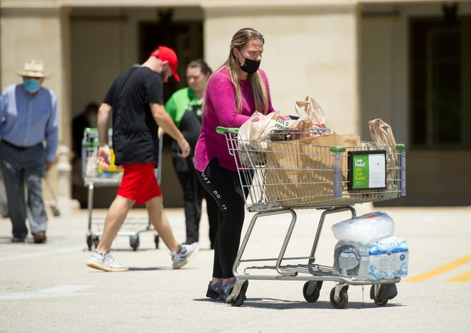 Shoppers stock up on bottled water and ice Tuesday at Publix in Palm Beach as a water advisory for West Palm, Palm Beach, South Palm remains in effect.