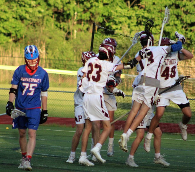 Portsmouth's Skyler Mikalietes (48), Owen Ingwerson (13) and Ryan Patte (23) celebrate with teammates, while Winnacunnet's James O'Hara walks off in disappointment following Portsmouth 8-7 victory in a Division II boys lacrosse play-in game on Monday at Tom Daubney Field