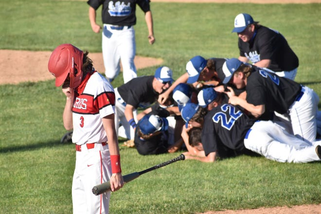 Pocono Mountain East's Carter Shook (left) returns to East's dugout as Southern Lehigh baseball players pile up to celebrate their district title victory in Center Valley on Monday, May 31, 2021. The Spartans defeated the Cardinals, 6-0.