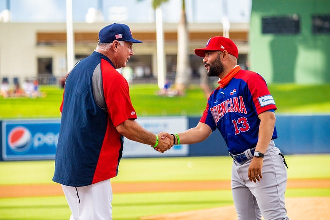 U.S. manager Mike Scioscia shakes hands with Dominican Republic manager Hector Borg before Tuesday's game at the Ballpark of the Palm Beaches. Julia Bonavita/Special To The Post