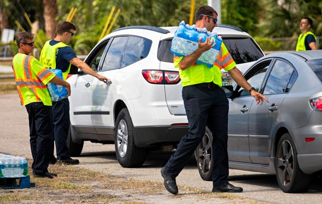 West Palm Beach firefighters distribute bottled water to residents at Gaines Park Tuesday, June 1, 2021. The city has issued an advisory that infants, young children and other vulnerable people in the city, as well as the towns of Palm Beach and South Palm, should not drink the tap water after discovering a toxin produced by blue-green algae in its water supply. The water distribution will continue Wednesday from 9 a.m. to noon at Gaines Park, 1501 Australian Avenue. Plans for further distribution are not yet in place.  Assistant Fire Chief and Emergency Manager Brent Bloomfield says the city has given out about 175,000 bottles of water since Friday.