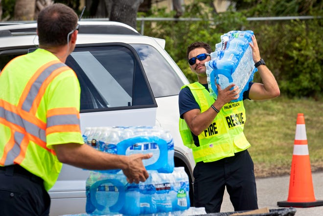 West Palm Beach firefighters distribute bottled water to residents at Gaines Park Tuesday, June 1, 2021.