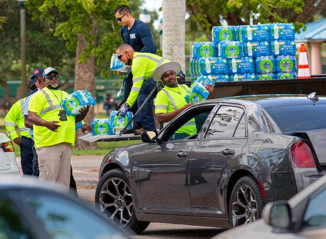 City of West Palm Beach firefighters and workers with several other departments hand out bottled water to residents at Gaines Park on May 29 after an algal toxin was discovered in the city's drinking water supply.