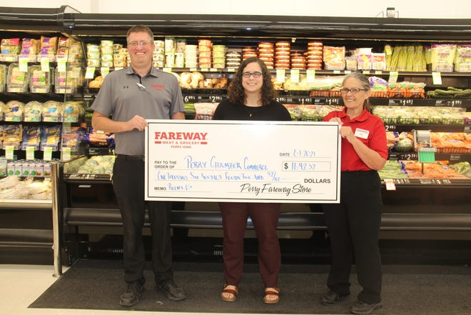 Fareway Store Manager Travis Landgrebe and checker Phyllis Manternach-Barr present a check to Perry Chamber of Commerce Executive Director Lynsi Pasutti  at the end of the round-up event for the Fourth of July Fireworks Drive.