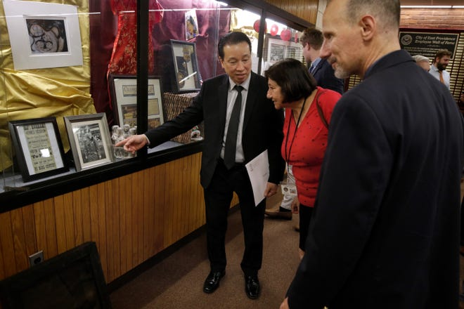 U.S. Marshal Wing Chau points to a photo in a display case honoring Asian-American and Pacific Islander heritage. He is with two members of the state attorney general's office: Ani Haroian, director of community engagement, and Ed Troiano, chief of the bureau of criminal investigation.