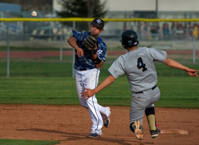 Bear Creek's Zack Mathis attempts to turn a double play after forcing out West's Jose Hernandez at second during a varsity baseball game on March 12, 2015.