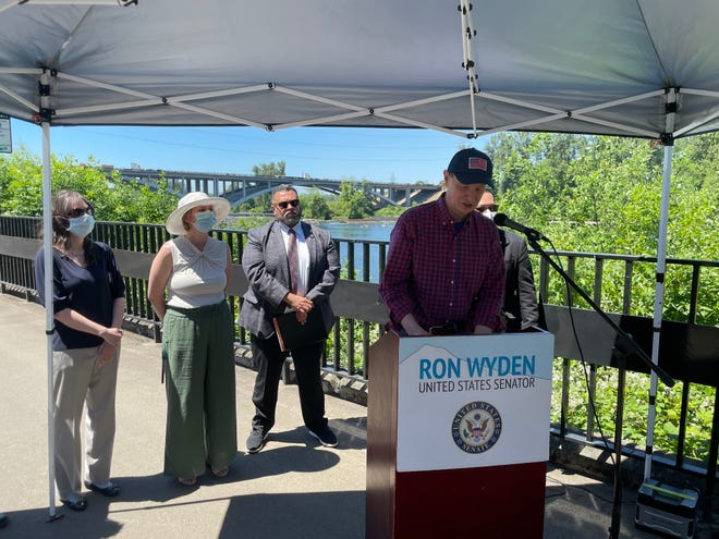 Sen. Ron Wyden speaks about the Build America Bonds program on Tuesday with the Whilamut Passage Bridge in the background.