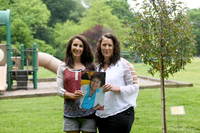 Sisters Amy Kubbins, left, and Sue King hold a photo of their mother, Betty Gossage, at Reservoir Park at the location of a newly planted tree  and plaque in her honor. A bench also will be installed.  The spot overlooking the playground is fitting, as Gossage loved and cared for children.