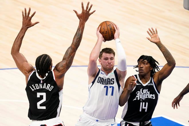 Los Angeles Clippers' Kawhi Leonard (2) and Terance Mann (14) defend as Dallas Mavericks guard Luka Doncic (77) drives to the basket in the first half in Game 4 of a first-round playoff series in Dallas last Sunday.