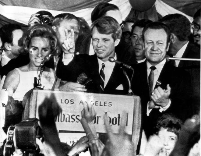 In this June 5, 1968, photograph, U.S. Sen. Robert F. Kennedy, D-N.Y., center, speaks to campaign workers on June 5, 1968, as his wife, Ethel, and California campaign manager and speaker of the California Assembly, Jesse Unruh, look on at the Ambassador Hotel in Los Angeles. After making a short speech, Kennedy was shot in an adjacent room.