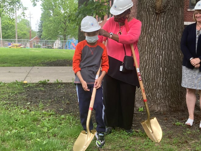 Former District 186 board of education member Judith Johnson helps Dubois Elementary third-grader Logan Thongsithavong adjust his hard hat at a groundbreaking ceremony at the school Tuesday morning. Dubois, the district's oldest building dating from 1896, will get several classroom additions and an elevator for the first time.