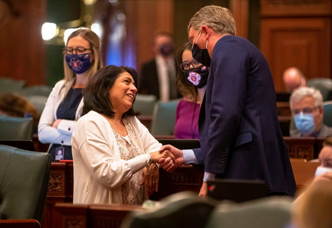 State Rep. Lisa Hernandez, D-Cicero, shakes hands with Illinois State Rep. Patrick Windhorst, R-Metropolis, after the passage of Senate Bill 667, the Illinois Way Forward Act that would close detention centers and prevent law enforcement from inquiring on immigration status, on the floor of the Illinois House of Representatives on the last day of session at the state Capitol on Monday. [Justin L. Fowler/The State Journal-Register]