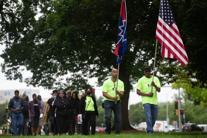 Rodney Harman, left, and Kevin Jordan, right, carry flags as they lead a march Tuesday around the Statehouse in honor of the Juneteenth holiday. Events are scheduled throughout the month, including a Juneteenth parade on June 12 and concert at Evergy Plaza on June 18.