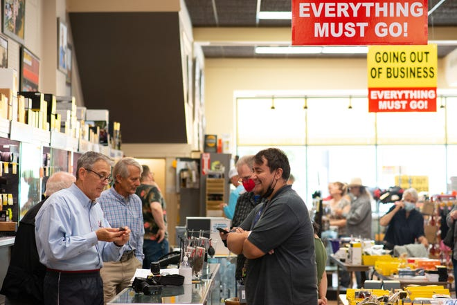 Helping customers with their camera questions, as he has for the past 40 years, DeWitt Harkness, left, president of Wolfe's Camera, said Tuesday's crowd of shoppers reminded him of the old days.