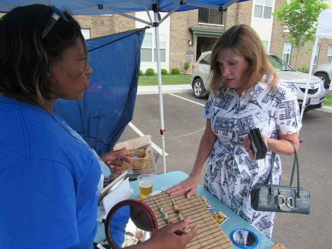 Shana Scott (left), owner of Iridescent Designs Jewelry, discusses her merchandise with Sharon Pantelis at the June 1 debut of Market on the Green at  the Kelley Green park in Whitehall.