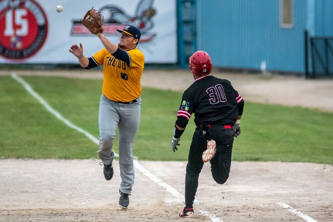 Roy Thurman (30) makes it safely to first base before Cooper Doughman (29) forces him out on Monday, May 31, 2021 at C.O. Brown Stadium in Battle Creek, Mich. The Growlers defeated the Bombers 6-2.