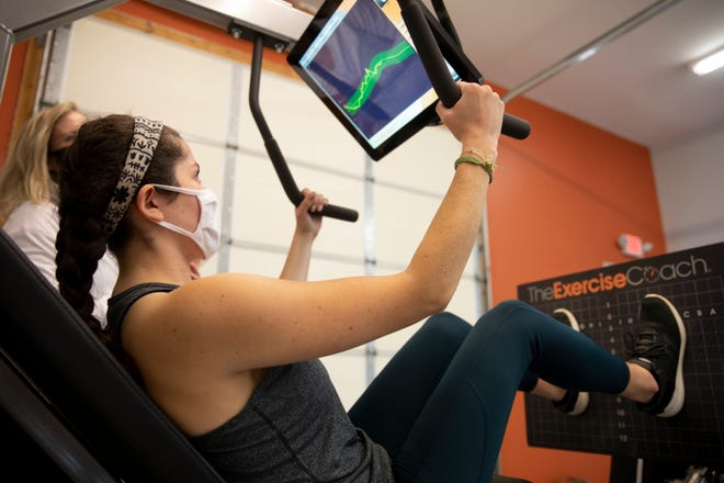 Maria Aguilar, Cincinnati Enquirer intern, tests out a leg machine at the Exercise Coach studio in West Chester, June 1, 2021. Billy Cottle and Veronica Sterling are opening the new gym beginning June 2. The strength training program is 20 minutes and is recommended twice a week. You follow the computer as you work out and it adjusts to your level and tracks your progress.