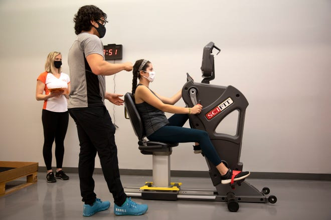 Maria Aguilar, Cincinnati Enquirer intern, tests out a cardio machine at the Exercise Coach studio in West Chester, June 1, 2021 as franchise owners Billy Cottle and Veronica Sterling give instruction.