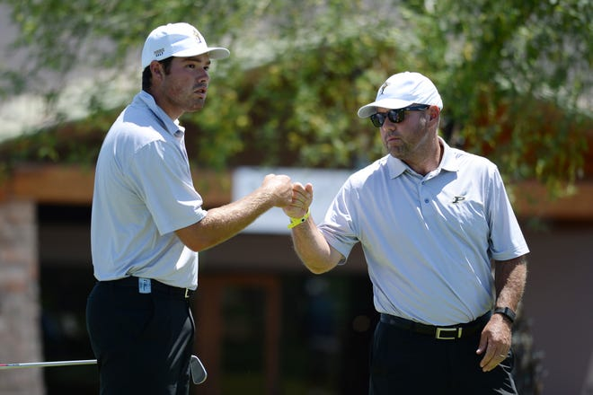 May 29, 2021; Scottsdale, Arizona, USA; Purdue University golfer Cole Bradley (left) bumps fist with head coach and father Rob Bradley at the tenth tee box during the NCAA Men's Golf Championship at Grayhawk Golf Club. Mandatory Credit: Joe Camporeale-USA TODAY Sports