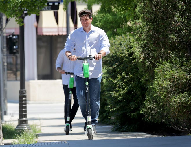 People ride Lime scooters down East Kilbourn Avenue in Milwaukee on Tuesday, June 1, 2021.