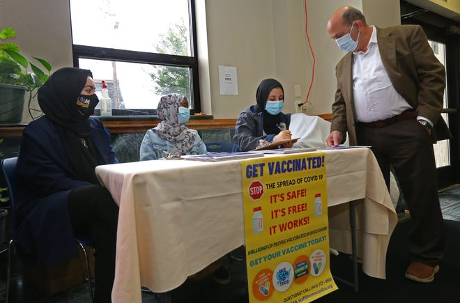 Basma Daham, seated right, does a short survey with Fahmi Abdallah, standing, while providing information on May 28, 2021, about getting vaccinated. Abdallah had received the vaccination. Daham along with, from left, Sarah Farhan and Hafsa Mohamed,  are part of the Milwaukee Muslim Women's Coalition through a state DHS grant that are working as vaccine educators in the Muslim community. They were on hand at the Islamic Society of Milwaukee at 4704 S. 13th St. and will be also going to such places at ethnic grocery stores to continue to share about the importance of getting the vaccine.