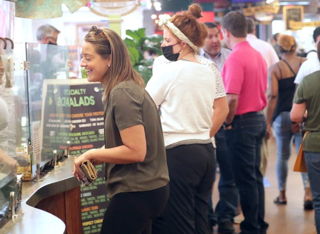 Lauren Zembrowski orders a salad at the Public Market on North Water Street in Milwaukee on Tuesday, June 1, 2021. The City of Milwaukee's mask ordinance ended on Tuesday, turning decisions about wearing face coverings over to individuals and businesses.