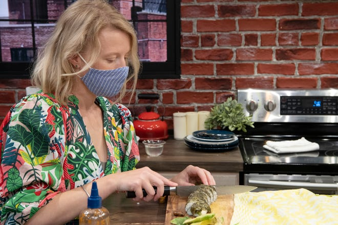 """Dr. Cortni Borgerson, Assistant Professor of Anthropology at Montclair State University, prepares and eats cicadas on Tuesday, June 1, 2021. Borgerson cuts a """"sushi roll"""" containing pan grilled cicadas."""