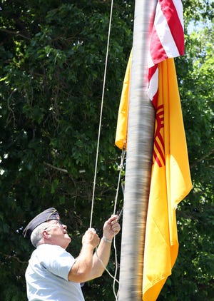 American Legion Bataan Post 4 Commander Thom Barry raises the flags at the World War II Memorial at Mountain View Cemetery on Monday.