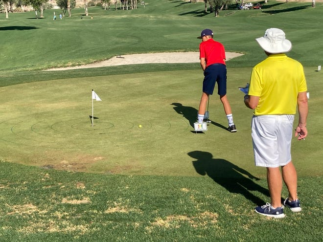 A volunteer watches as a golfer takes his six-foot putt during the Drive, Chip and Putt competition Sunday at The Golf Center at Palm Desert. Golfers earn points from three different putting distances.