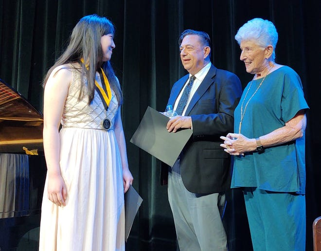 Graduating senior Isabella Cao receives accolades from Jim McCormick, director of the Festival Awards program, and Ruth Moir, founder and CEO of the Steinway Society of Riverside County.