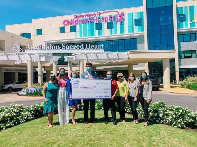 Will Condon (center), president of the Studer Family Children's Hospital at Ascension Sacred Heart, celebrates the Cordova Mall Ball donation with members of the Krewe of Les Petits Enfants (Cordova Mall Ball Committee) and Ascension Sacred Heart Foundation.