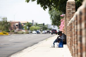 A woman sits under a patch of shade along Seventh Avenue as temperatures reach 103 degrees in Phoenix on June 1, 2021.