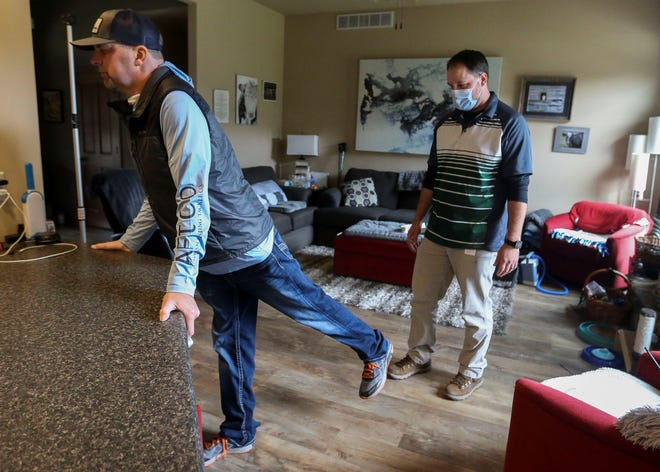 Eric Walters, left, goes through hip abductor exercises with physical therapist Eric Napiwocki on April 27 at Walters's home near Stevens Point. Walters was diagnosed with an autoimmune disease that attacks his brain and impacts his speech, vision, muscular coordination and ability to breathe.