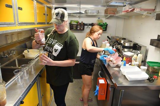 La propietaria Deidra Stewart, a la izquierda, prepara una bebida de café con caramelo mientras Ramona Rainbolt cocina un gofre gourmet en el nuevo tráiler de Chicka D's Coffee en Brook Avenue el martes 1 de junio de 2021. El café móvil es el segundo para el negocio de Stewart.