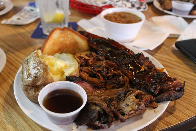 A combo dinner of pulled pork, brisket and ribs is served with two sides and Texas toast at Main Street Saloon in Akron.