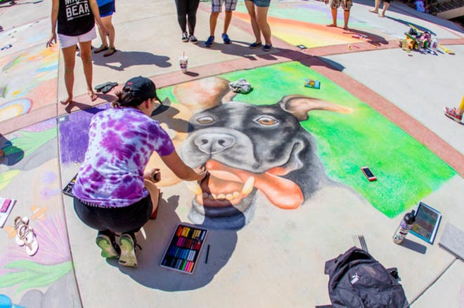 A sidewalk chalk artist puts the finishing touches on her entry during a previous Amarillo College Chalk It Up art contest. This year's event is scheduled for July 31 at the Washington Street campus.