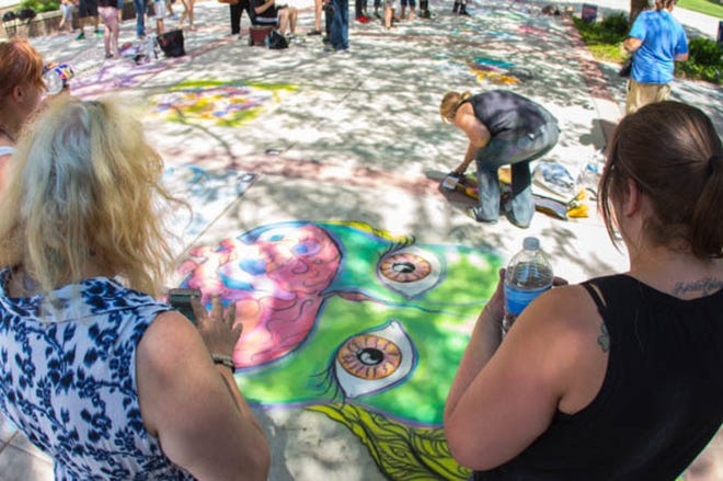 Spectators look on as a chalk artist completes a project during a past Chalk It Up Amarillo College art contest.