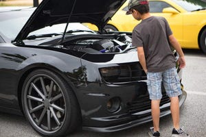A child looks under the hood of a Chevy Camaro at a 2019 Coffee and Cars Augusta event at the Augusta-Richmond County Judicial Center. Coffee and Cars Augusta will race at Carolina Speedway on Dragstrip Road in Aiken on Saturday from 5 to 11 p.m.