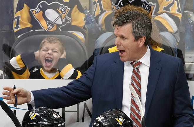 Pittsburgh Penguins head coach Mike Sullivan, right, gives instructions as a young fan reacts during the overtime period of an NHL hockey game against the New York Islanders in Pittsburgh, Saturday, March 3, 2018. Sullivan appears to be returning as coach next year despite his team's fourth early playoff exit in a row. (AP Photo/Gene J. Puskar)